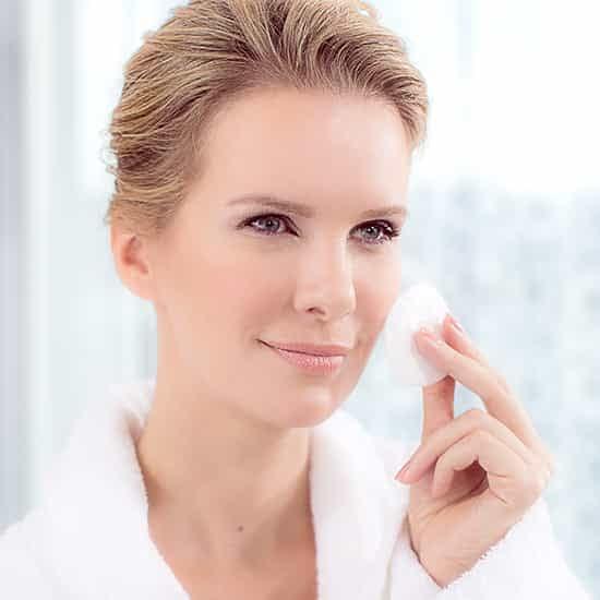 Lady rubbing skin with Miravera® - Refreshing Skin Water